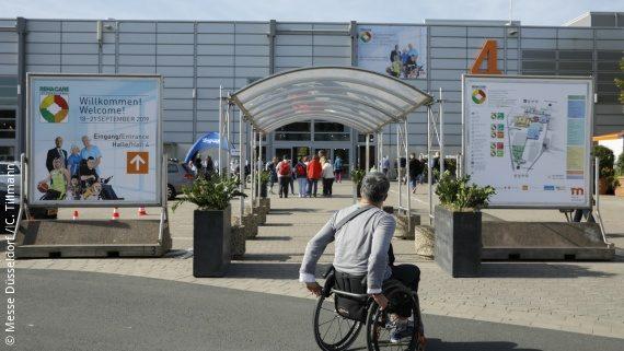 Photo: a man in a wheelchair in front of a Düsseldorf trade fair building; Copyright: Messe Düsseldorf / C. Tillmann