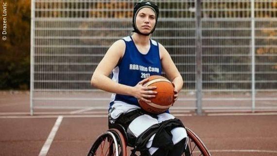 Foto: eine junge Frau in einem Sportrollstuhl auf einem Basketballfeld, sie trägt ein blaues Trikot und einen Kopfschutz, in den Händen hält sie einen Basketball – Ronja Holze;Copyright: Drazen Lovric