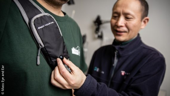 Photo: a person wearing a device that looks like a backpack on the chest; Copyright: Mass Eye and Ear