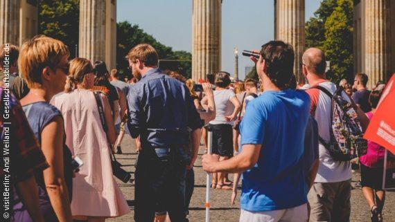 Foto: ein Mann mit Weißem Langstock steht vor dem Brandenburger Tor; Copyright: visitBerlin; Andi Weiland | Gesellschaftsbilder.de