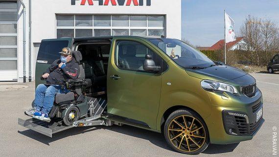 Foto: ein Mann mit Elektrorollstuhl vor einem grünen umgebauten Auto; Copyright: PARAVAN
