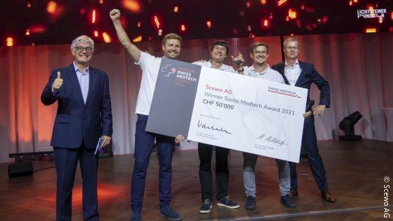 Foto: vier Männer der Scewo AG stehen auf einer Bühne und halten einen großen Scheck; Copyright: Scewo AG