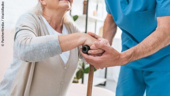 Foto: eine ältere Frau mit Gehstock wird von einer pflegenden Person gestützt; Copyright: PantherMedia / VitalikRadko