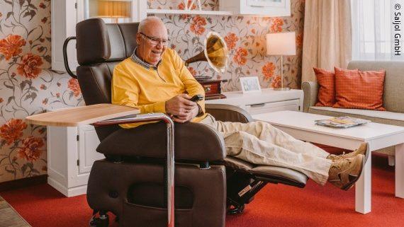 Foto: ein Mann sitzt in einem großen braunen Sessel und hat die Füße hochgelegt; Copyright: Saljol GmbH