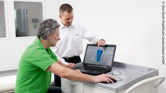 Photo: A technician sits in front of a laptop showing a scanned knee. An Ottobock employee stands next to him and explains something to him; Copyright: Otto Bock HealthCare Deutschland GmbH