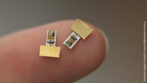 Photo: a tiny tech implant about the size of a Cent on a finger; Copyright: Secure and Intelligent Micro-Systems Lab/Rice University