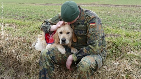 Photo: a soldier leaning his head against his dog; Copyright: Rehahunde Deutschland e.V.