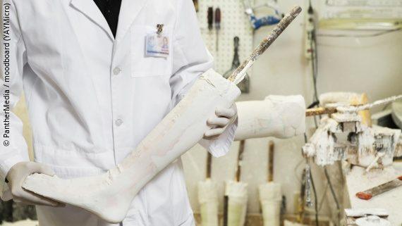 Foto: Ein Orthopädietechniker hält ein Gipsbein aus der Werkstatt in seinen Händen; Copyright: PantherMedia / moodboard (YAYMicro)