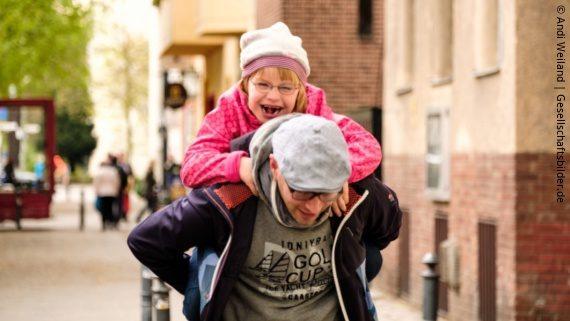 Foto: ein Vater trägt seine Tochter mit Behinderung auf dem Rücken; Copyright: Andi Weiland | Gesellschaftsbilder.de