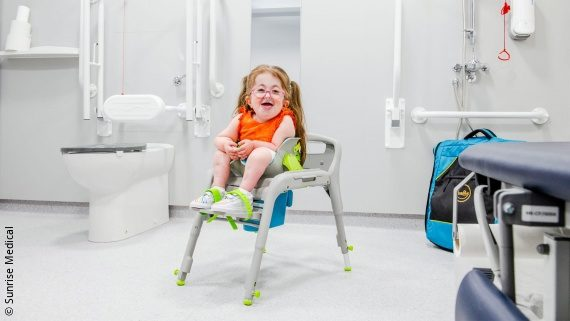 Photo: a girl with bangs and an orange tshirt is sitting in an toilet seat and smiling at the camera; Copyright: Sunrise Medical