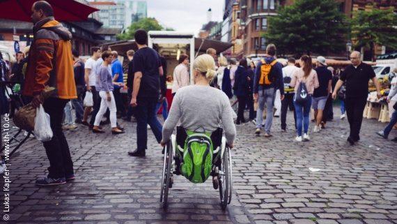 Foto: Eine Rollstuhlfahrerin fährt auf Kopfsteinpflaster auf eine größere Menschenmenge auf einem Markt zu; Copyright: Lukas Kapfer | www.th-10.de