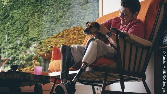 Photo: Young man in a cosy armchair with his dog on his lap. He is wearing a prosthetic leg.; Copyright: PantherMedia/DGLimages