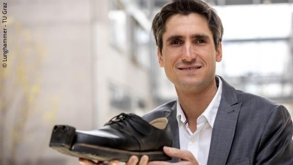 Photo: a man in a grey suit is holding a shoe with a build-in camera; Copyright: Lunghammer - TU Graz