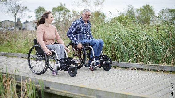 Foto: Zwei Rollstuhlnutzende in Outdoor-Kleidung bewegen sich auf einem Steg.; Copyright: So Yes