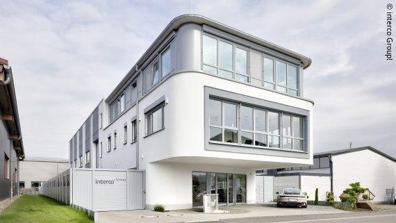 Foto: ein weißes mehrstöckiges Gebäude, am Zaun die Aufschrift