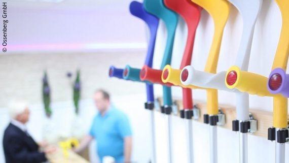 Foto: bunte Gehhilfen sind an einer Wand fixiert, im Hintergrund findet ein Beratungsgespräch statt; Copyright: Ossenberg GmbH