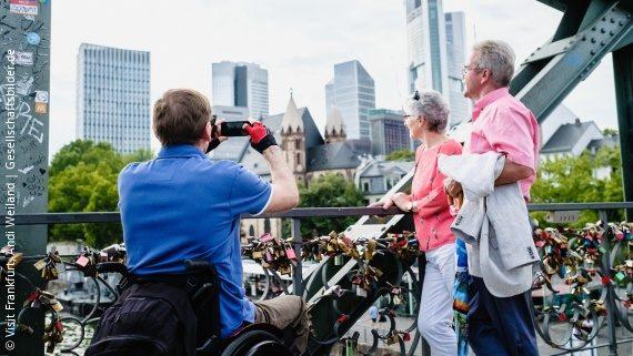 Photo: male wheelchair user taking a picture of an elderly couple in front of the Frankfurt am Main skyline; Copyright: Visit Frankfurt, Andi Weiland | Gesellschaftsbilder.de
