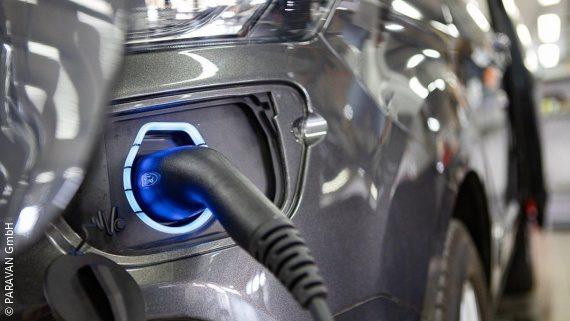Foto: Ein anthrazitfarbener Ford Tourneo, der gerade an der Ladestation hängt und aufgeladen wird; Copyright: PARAVAN GmbH
