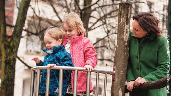 Foto: zwei Kinder stehen auf einem Spielplatz-Gerüst, hinter ihnen steht die Mutter; Copyright: Andi Weiland   Gesellschaftsbilder.de