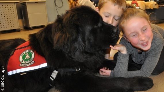 Image: two children are laying on the ground, petting a black newfoundland dog; Copyright: UBC Okanagan