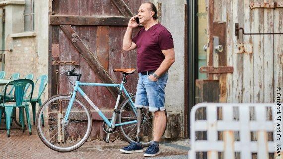 Foto: ein Mann steht telefonierend vor eine Scheune, er trägt eine Unterschenkel-Prothese; Copyright: Ottobock SE & Co. KGaA