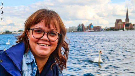Foto: eine Frau mit schultelangem Bild Haar und Brille schaut von links ins Bild, hinter ihr ist das Meer zu erkennen – Anne Schütz; Copyright: Holger Schütz