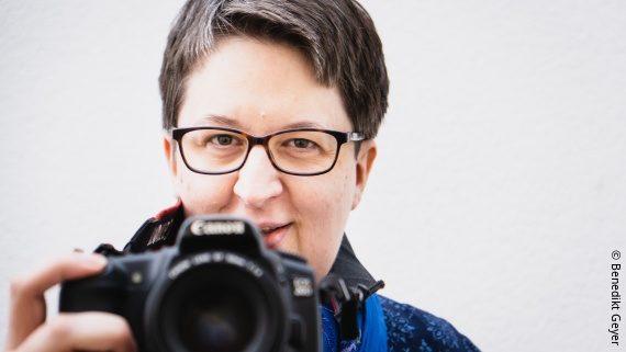 Foto: eine Frau mit Brille und grauen Haaren steht hinter einer Kamera – Annette Schwindt; Copyright: Benedict Geyer