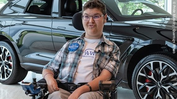 Photo: 17 year old Austyn Martin with his new power wheelchair in front of an Aston Martin; Copyright: Pride Mobility | Quantum Rehab
