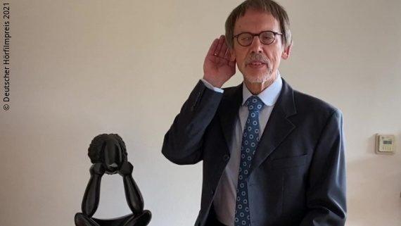 Foto: ein Mann sitzt auf einer Kommode und formt seine Hand am Ohr zu einer Muschel – Klaus Hahn; Copyright: Deutscher Hörfilmpreis 2021