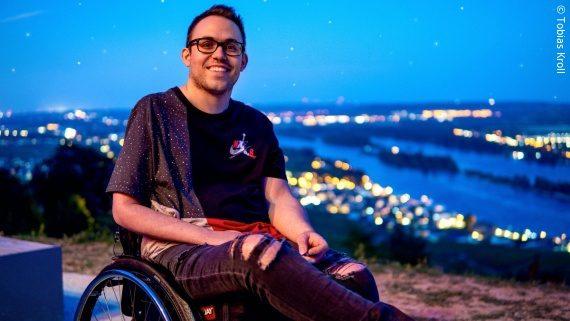 Foto: ein junger Mann mit Brille und Jeans im used-Look sitzt in einem Rollstuhl in der Dämmerung auf einer Anhöhe, im Hintergrund ist ein Fluss zu sehen – Tobi Kroll; Copyright: Tobias Kroll