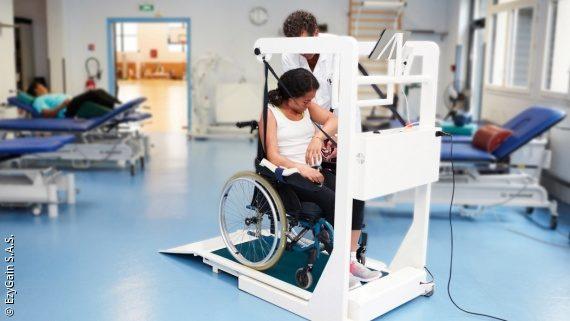Foto: eine Frau fährt mit ihrem Rollstuhl auf ein Laufband, ein Physiotherapeut steht neben ihr und hilft ihr; Copyright: ezyGain S.A.S.