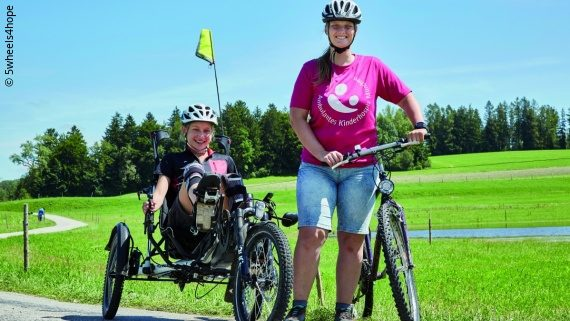 Foto: eine Frau neben ihrem Fahrrad und ein Mädchen in einem Liegerad; Copyright: 5wheels4hope
