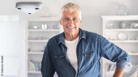Photo: a man with white hair and blue shirt smiles to the camera, a white Patronusens-box is installed at the ceiling; Copyright: Inferics GmbH