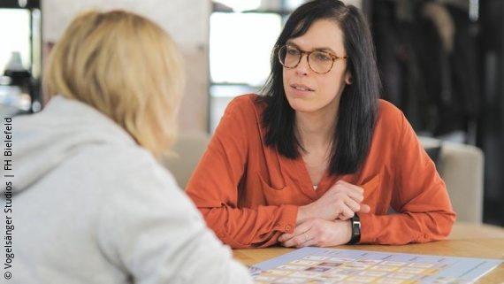 Foto: Zwei Frauen sitzen an einem Tisch und besprechen den wöchentlichen Bewegungsplan; Copyright: Vogelsänger Studios | FH Bielefeld
