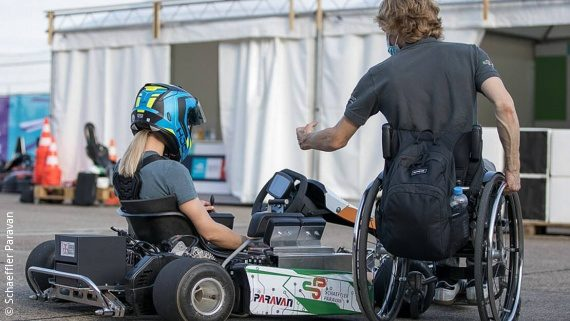 Foto: ein Kind mit Helm sitzt in einem Kart, daneben sitzt ein Mann im Rollstuhl und erklärt etwas; Copyright: Schaeffler Paravan