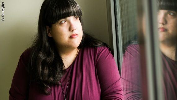 Photo: a woman with dark hair and a purple shirt is looking outside a window – Heike Schlemmer; Copyright: Kai Myller