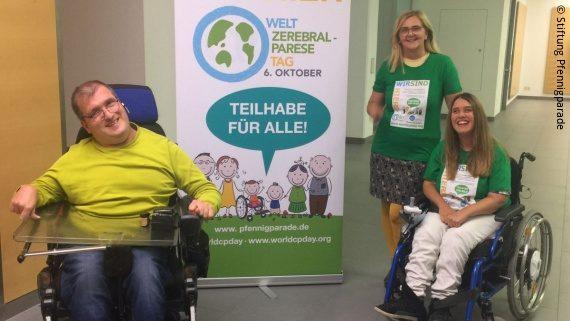 Foto: Thomas Müller, Beate Höß-Zenker und Janine Aigner stehen vor und neben einem großen Plakat zum Welt-Zerebralparese-Tag 2021; Copyright: Stiftung Pfennigparade