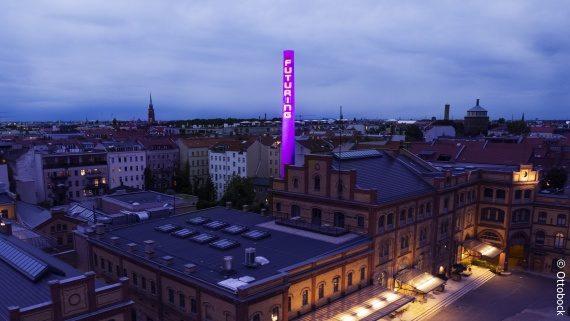 Foto: ein Werksgelände in Berlin, ein großer Schornstein ist in lila mit dem Wort