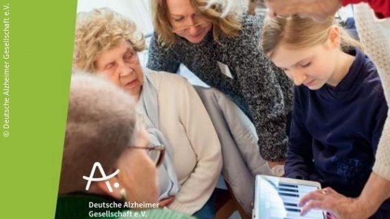 Foto: ältere und jüngere Menschen stehen um ein Tablet herum; Copyright: Deutsche Alzheimer Gesellschaft e.V.