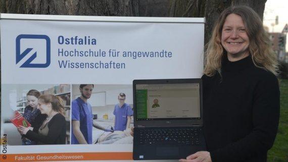 Foto: eine Frau steht im Freien vor einem Plakat und hält einen Laptop-Bildschirm Richtung Kamera; Copyright: Ostfalia