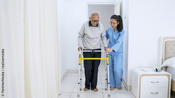 Photo: an older man is using a walking aid, a woman is helping him; Copyright: PantherMedia / Realinemedia
