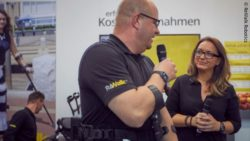 Foto: Mela Ikanovic und ein ReWalker am Messestand von ReWalk Robotics; Copyright: ReWalk Robotics