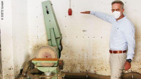 Foto: ein Mann steht vor einer verschlammten Wand und markiert mit seinem rechten Arm die Wasserstandshöhe der Flut in den Räumlichkeiten; Copyright: DIETZ GmbH