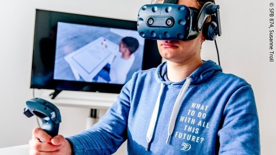 Photo: a young man wearing a VR headset and holding a joystick; Copyright: SFB 874, Susanne Troll