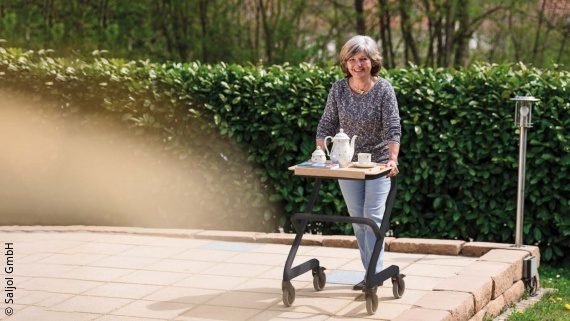 Foto: eine Frau mit kinnlangem Haar schiebt auf einer Terrasse einen schwarzem Rollator vor sich her, darauf steht ein Tablett; Copyright: Saljol GmbH