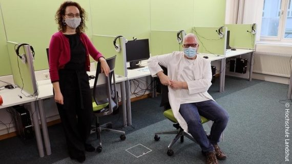 Photo: a woman and a man in a room with computers, both are wearing a face covering mask; Copyright: Hochschule Landshut