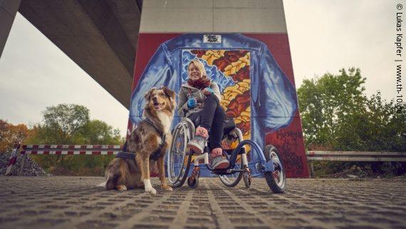 Foto: Eine junge Frau im Rollstuhl unter einer Brücke vor einem Graffito. Neben ihr sitzt ihr Australian Sheperd; Copyright: Lukas Kapfer | www.th-10.de