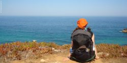 Foto: Theresa Steinkellner sitz mit Rucksack vorm Meer in Portugal; Copyright: privat