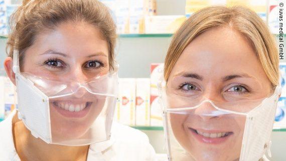 Foto: zwei Frauen in einer Apotheke tragen durchsichtige Masken, mit denen die Kommunikation für Menschen mit einer Hörbehinderung leichter macht; Copyright: iuvas medical GmbH