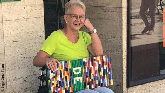 Photo: a woman with light grey hair, glasses and a green t-shirt is sinnting in a wheelchair in front of a building, on her legs she carries a ramp made of tiny bricks; Copyright: Lego-Oma-Team